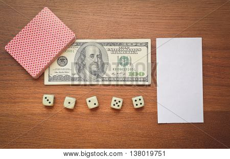 hundred dollars and playing cards with dice