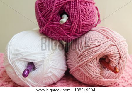 Three balls of wool with crochet needles