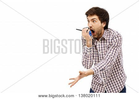 Close-up portrait of handsome amused young blue-eyed dark-haired man screaming in walkie-talkie wearing casual plaid shirt. Isolated.