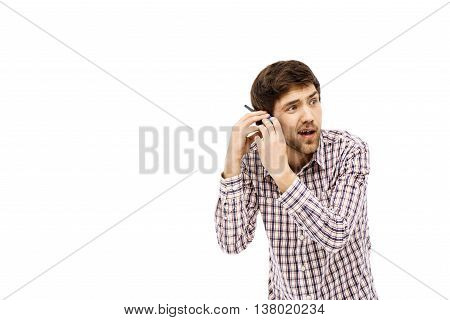 Close-up portrait of handsome amused young blue-eyed dark-haired man with walkie-talkie wearing casual plaid shirt. Emotional funny face. Isolated.
