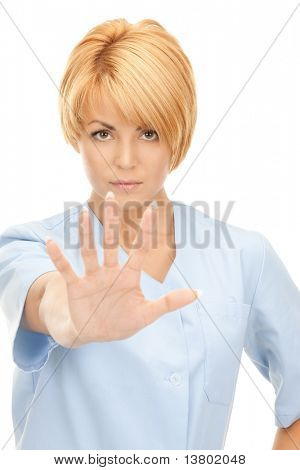 bright picture of attractive female doctor showing stop gesture