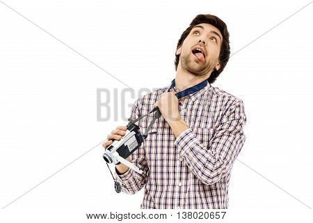 Close-up portrait of handsome young blue-eyed, dark-haired man strangling himself by the handy cam belt, with open moth and  protruding tongue, wearing casual plaid shirt. Isolated.