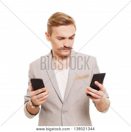 Young blond man with mustache choose between two cell phones. Guy looks at mobile, selecting which to buy. Comparing smartphones in hands. Male portrait isolated at white background