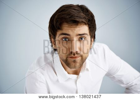 Close up portrait of elegant handsome young businessman in white shirt staring at camera. Studio, isolated on grey background.