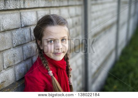 girl in red raincoat near concrete fence outdoor