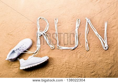 White running shoes and run sign made of shoelaces against sand background, studio shot, flat lay