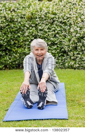 Senior woman doing her stretches in the garden