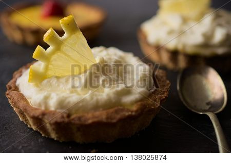 Delicious dessert fresh cheese and lemon tart decorated with lemon slice on dark stone slate. Selective focus on lemon slice. Concept of Home baking. Concept of home made desserts.
