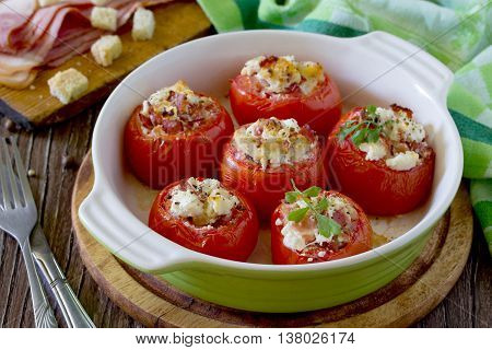 Baked Stuffed Tomatoes With Bacon And Feta Cheese On A Wooden Table