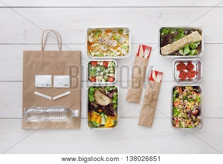 Healthy food delivery. Take away of natural organic low carb diet. Fitness nutrition in foil boxes, cutlery and brown paper package. Top view, flat lay at white wood