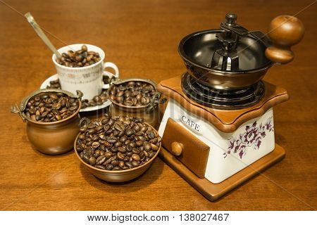 Grinder with coffee beans in copper bowls and Cup