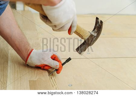 Laying hardwood parquet. Worker put the nail using a hammer.