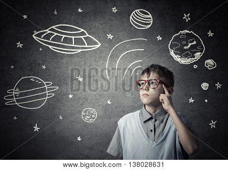 Cute boy of school age dreaming he is astronaut