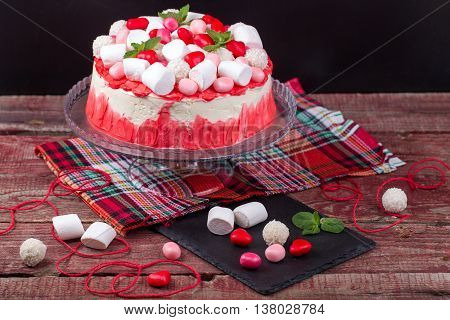 Tasty biscuit cake decorated to a marshmallow colourful coconut balls and candies
