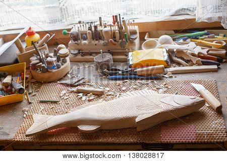 handmade carved wooden fish in the workshop. the unfinished carpentry work. fish carved from wood