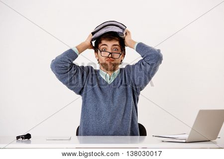 Handsome tired young businessman in glasses and headphones having a break sitting at the office desk. Looking at camera. Isolated on white background.