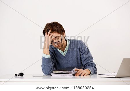 Handsome tired young businessman in glasses sitting at the office desk. Looking away. Isolated on white background.