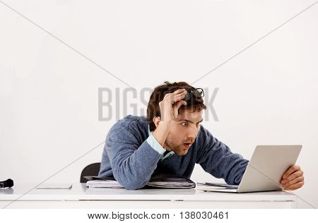 Handsome shocked young businessman in glasses sitting at the office desk staring at screen of his laptop. Isolated on white background.