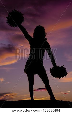 a silhouette cheerleader holding an angle with her arms and pom poms.