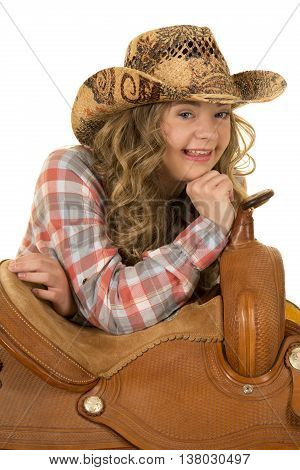 A cowgirl with down syndrome with a big smile laying on a saddle.