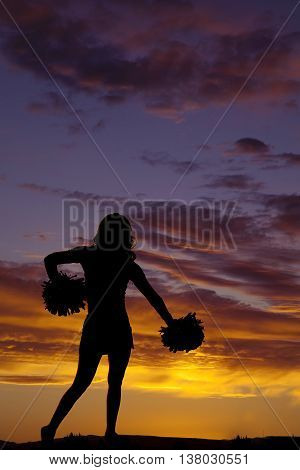 A silhouette of a cheerleading girl with her pom poms.