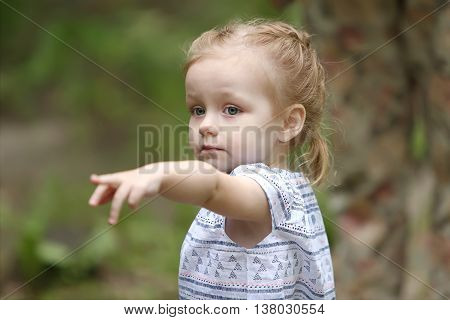 Little pretty girl pointing direction by finger