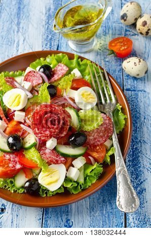 Salad with fresh vegetables feta cheese quail eggs olives and salami. Plate with salad on a blue wooden background