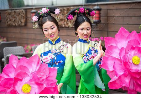 Two Asian girls in traditional Chinese dresses with umbrellas in the form of lotus flowers