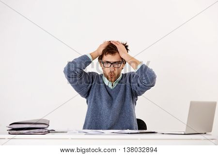 Handsome tired young businessman in glasses sitting at the office desk with hands over his head. Looking at camera. Isolated on white background.