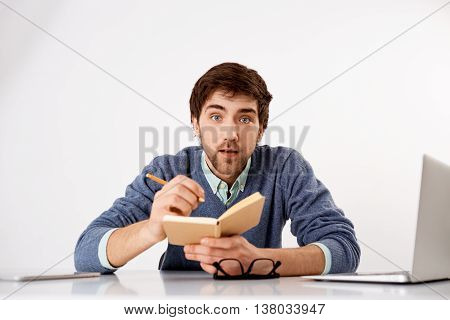 Handsome surprised concentrated young businessman sitting at the office desk writing down something to notebook with a pencil. Looking at camera. Isolated on white background.
