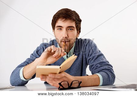 Handsome confident young businessman sitting at the office desk with notebook in his hands biting pencil. Looking at camera. Isolated on white background.