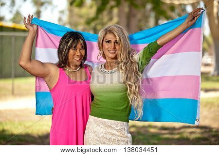 Transgender females holding Pride flag behind them. Proud to be who they are.