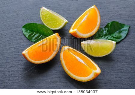 Orange and lime sliced segments with green leaves on black slate stone