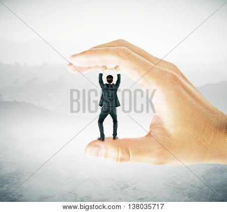 Businessman trapped between fingers of big hand on abstract grey landscape background. Pressure concept