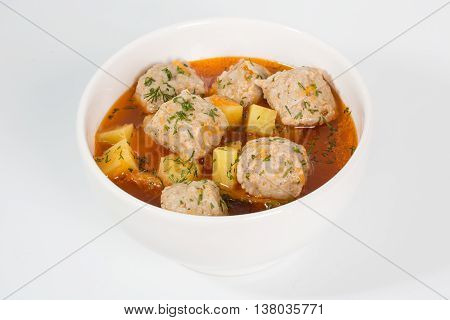 Meatballs in gravy with roast potatoes and vegetables.