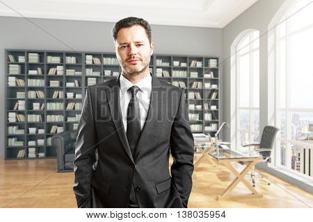 Handsome young businessman looking at the camera in library interior with large bookshelf workplace and city view