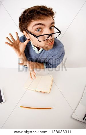 Funny and crazy handsome young businessman in glasses sitting at the office desk on white background. Looking at camera. Wide angle.