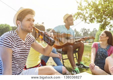 Happy young people making picnic together. Man is playing guitar while women are singing. Their friend is drinking beer with relaxation. They are smiling
