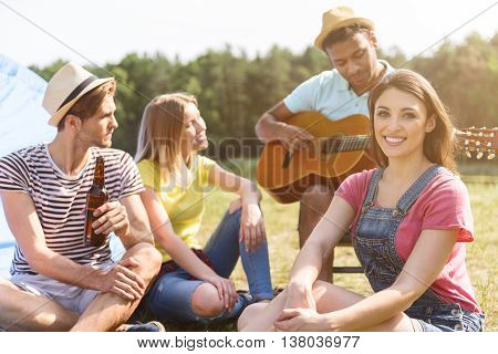 Carefree man is playing guitar with inspiration. His friends are listening music and smiling. They are sitting and resting in nature