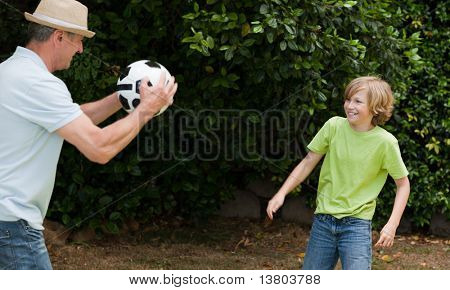Grandfather and his grandson playing football