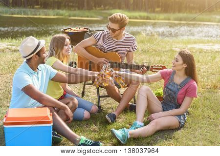 Lets drink for us. Cheerful young friends are celebrating event near river. They are clinking glasses and smiling. Man is sitting and playing guitar