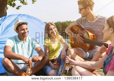 Joyful men and women having fun in nature. They are sitting on grass and drinking beer. Man is playing guitar and smiling