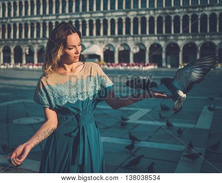 Beautiful well-dressed woman feeding pigeons on San Marco square.