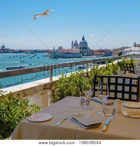 View from the restaurant on the cityscape of Venice and Grand Canal with Santa Maria della Salute church.