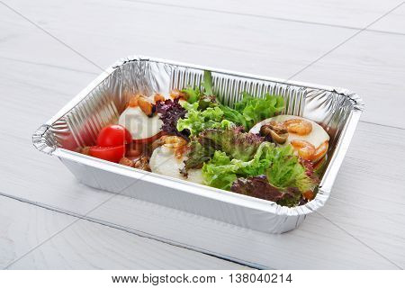 Healthy food and diet concept. Take away of fitness meal. Weight loss nutrition in foil boxes. Vegetables, lettuce and mozarella cheese with cherry tomatoes and shrimps at white wood
