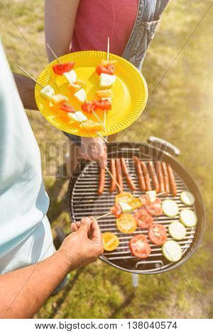 Top view close up of male hands taking vegetable barbecue from grill. Man and woman are standing on grass in the nature