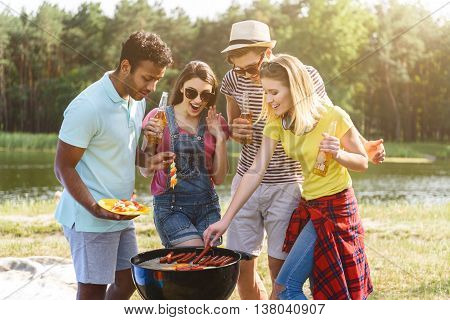 Happy young friends are making barbecue in the nature. They are standing near grill and smiling. Men and women are drinking beer