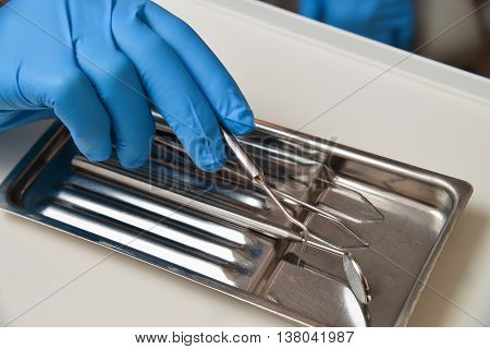 Professional woman dentist doctor working with dental instruments.