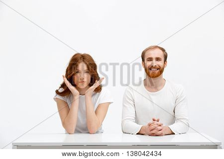 Funny redhead boy and seriously redhead girl sitting at white desk over white background.
