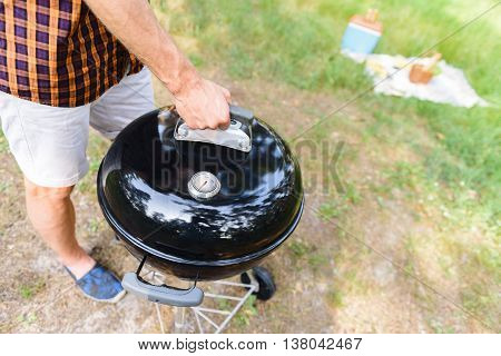 Close up of male arm opening grill for cooking. Man is standing on grass in nature